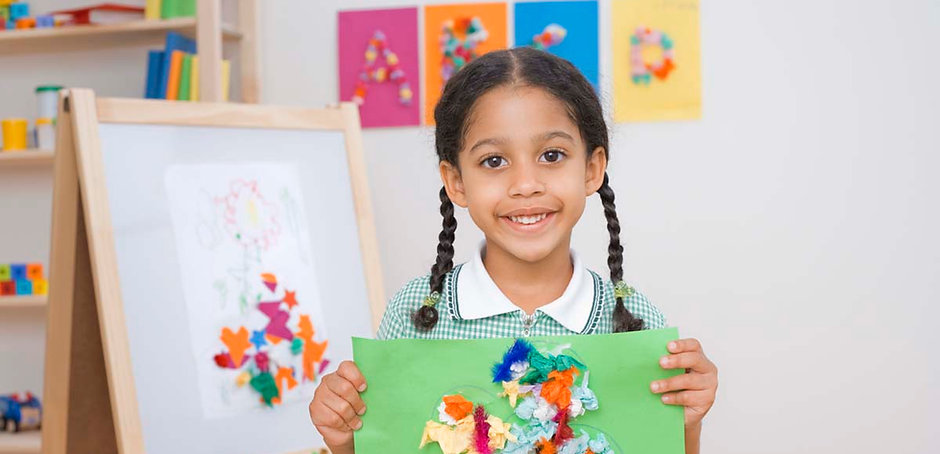 Young girl holding up tissue paper art project