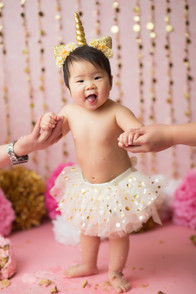 Newborn Photographer, baby photographer, family photographer, Pink Backdrop, gold pom poms, gold decorations, gold balloons, pink balloons, pink pom poms, pom poms, one year old girl, cake ,cake smash, pink rosette cake, gold head band, white tutu, mom and dad