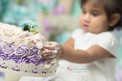 baby photographer, one year old, girl, cake smash, garden, blue, purple, green. blue floral hair clips, white dress, rosette cake, lavender