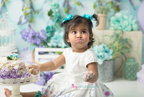 baby photographer, one year old, girl, cake smash, garden, blue, purple, green. blue floral hair clips, white dress,