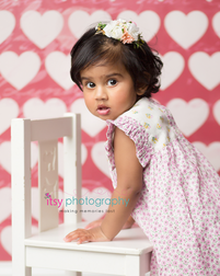 baby photographer, one year old girl, heart backdrop, white chair, floral dress, floral headband