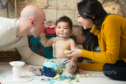 baby photographer, cake smash, blue rosette Cupcake, one year old boy, messy, white cake stand, map backdrop, hot air balloon, suspenders, hat, bow tie, suitcases, mom and dad, yellow  sweater