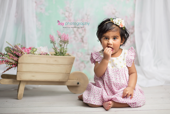 baby photographer, one year old girl, floral backdrop, white chair, floral dress, floral headband, white curtains, wheelbarrow, flowers