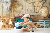 baby photographer, cake smash, blue rosette Cupcake, one year old boy, messy, white cake stand, map backdrop, hot air balloon, suspenders, hat, bow tie, suitcases, falling cake
