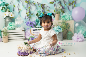 baby photographer, one year old, girl, cake smash, garden, blue, purple, green. blue floral hair clips, white dress