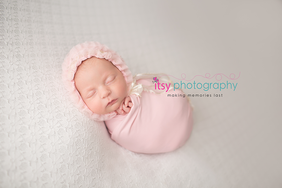 Newborn photographer, baby photography, infant photography, newborn girl, white backdrop, pink wrap, baby wrapping, pink and white banner,  newborn posing ideas, pink bonnet