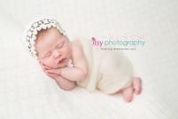 Newborn photographer, baby photography, infant photography, newborn girl, cream backdrop bow, head on hands pose, newborn posing, lace bonnet