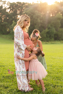 Maternity, pink maternity dress, daughters, kissing belly, outdoors, golden hour