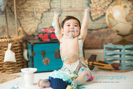 baby photographer, cake smash, blue rosette Cupcake, one year old boy, messy, white cake stand, map backdrop, hot air balloon, suspenders, hat, bow tie, suitcases, messy, blobe