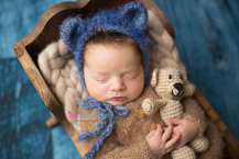 Newborn photographer, baby photographer, newborn, boy, infant, blue wood backdrop, wooden crib, white blanket, blue bear hat, bear, prop, brown fuzzy onsie