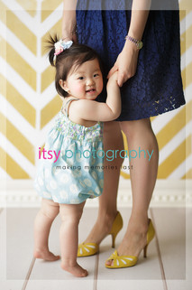 baby photographer, family photographer, one year old girl, , mom and daughter, yellow wallpaper backdrop, blue polka dot romper, dark blue dress