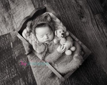 Newborn photographer, baby photographer, newborn, boy, infant, black and white, new born posing ideas, wooden floor backdrop, crib, bear, props, bear hat, fuzzie onsie
