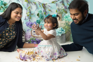 baby photographer, one year old, girl, cake smash, garden, blue, purple, green. blue floral hair clips, white dress, mom and dad