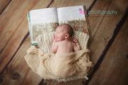 Newborn photographer, baby photography, infant photography, newborn boy, cream wrap, white blanket, book, wooden floor backdrop