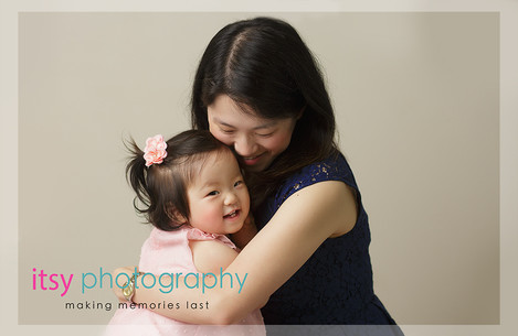 baby photographer, family photographer, one year old girl, , mom and daughter, cream backdrop, pink dress, dark blue dress