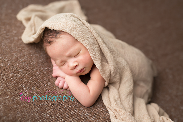 Newborn photographer, baby photography, infant photography, newborn boy, brown backdrop, cream wrap, newborn posing ideas, baby wrapping, head on hands pose.