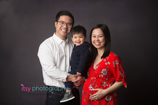 Maternity photography,  floral  maternity dress, studio session,  newborn photographer, maternity posing ideas, mom , black backdrop, red maternity dress, mom and dad, toddler, big brother