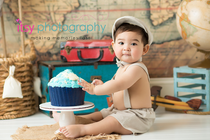 baby photographer, cake smash, blue rosette Cupcake, one year old boy, messy, white cake stand, map backdrop, hot air balloon, suspenders, hat, bow tie, suitcases