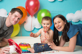 baby photographer, rainbow cake smash, rainbow cake, one year old boy, messy, red cake stand, rainbow balloons, cloud backdrop, mom, dad, family