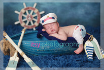 Newborn photographer, baby photography, infant photography, newborn boy, grey flokati, blue wrap, baby wrapping, newborn posing ideas, white chair, banner, blue backdrop, nautical, boat, oars, wheel, captain