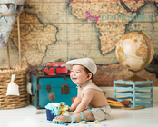 baby photographer, cake smash, blue rosette Cupcake, one year old boy, messy, white cake stand, map backdrop, hot air balloon, suspenders, hat, bow tie, suitcases, globe, messy, happy
