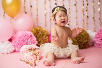Newborn Photographer, baby photographer, family photographer, Pink Backdrop, gold pom poms, gold decorations, gold balloons, pink balloons, pink pom poms, pom poms, one year old girl, cake ,cake smash, pink rosette cake, gold head band, white tutu