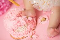 Newborn Photographer, baby photographer, family photographer, Pink Backdrop, gold pom poms, gold decorations, gold balloons, pink balloons, pink pom poms, pom poms, one year old girl, cake ,cake smash, pink rosette cake, gold head band, white tutu, foot in cake