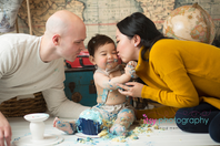 baby photographer, cake smash, blue rosette Cupcake, one year old boy, messy, white cake stand, map backdrop, hot air balloon, suspenders, hat, bow tie, suitcases, globe, messy, mom and dad