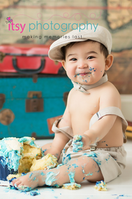 baby photographer, cake smash, blue rosette Cupcake, one year old boy, messy, white cake stand, map backdrop, hot air balloon, suspenders, hat, bow tie, suitcases, globe, messy