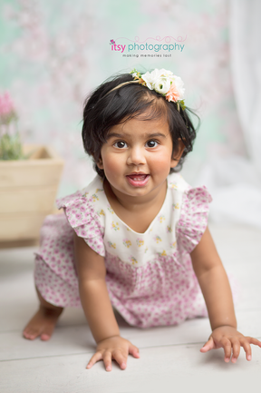 baby photographer, one year old girl, white chair, floral dress, floral headband