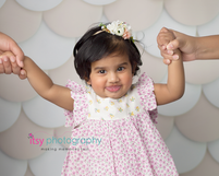 baby photographer, one year old girl,  cream backdrop, white chair, floral dress, floral headband, mom and dad