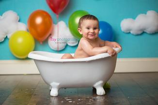 baby photographer, one year old, boy, bath, rainbow balloons, blue backdrop, bathtub, prop