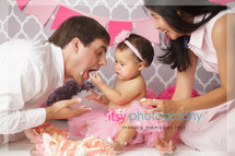 Newborn photographer, baby photography, infant photography, one year old girl, studio photography, cake smash, rosette floral cake, pop poms, grey wallpaper backdrop, pink banner,white cake stand, pink tutu , mom and dad