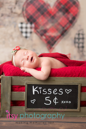 Newborn photographer, baby photography, infant photography, newborn girl, heart backdrop, valentines, red blanket, crate, chalk board, kissing booth, floral headband, head on hands pose, newborn posing ideas, wooden floor backdrop