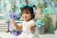 baby photographer, one year old, girl, cake smash, garden, blue, purple, green. blue floral hair clips