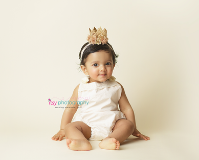 baby photographer,  baby girl, one year old, first birthday, cake smash, crown, white onsie, cream backdrop