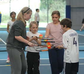 Children learning to play tennis