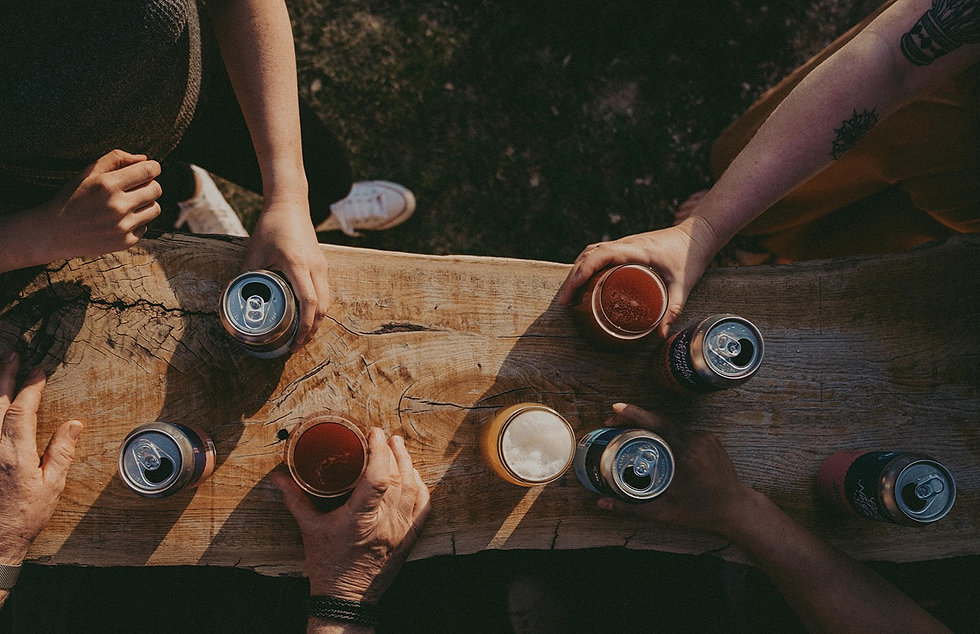top down view of a group of people standing at a bar enjoying a variety of beers