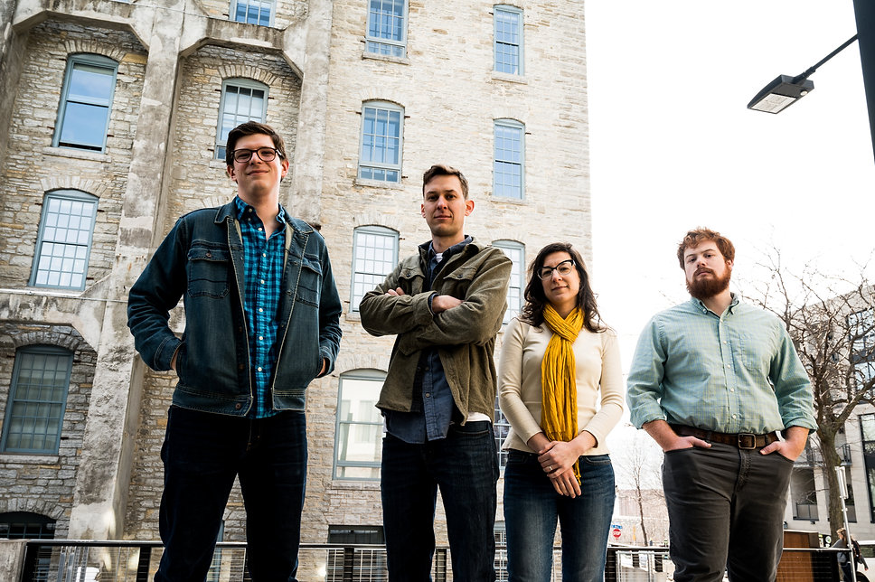 four band members stand in front of a tall stone building in Minneapolis