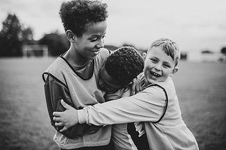 Junior football team hugging each other.