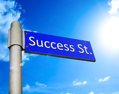 Road%20sign%20in%20front%20of%20a%20blue%20summer%20sky%20showing%20the%20way%20to%20Success%20Stree