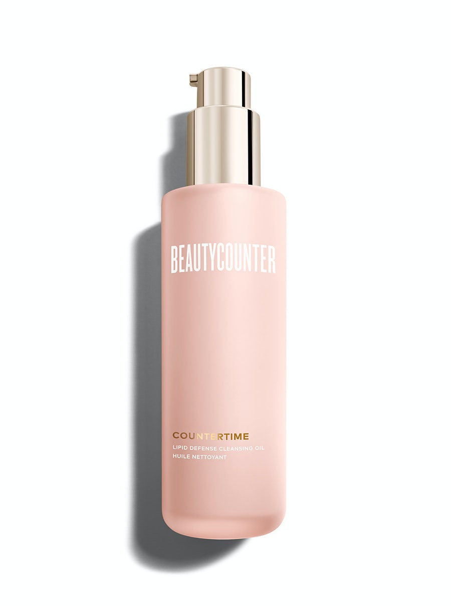 A powdery pink bottle of Beautycounter Lipid defense cleansing oil with a gold-tone pump