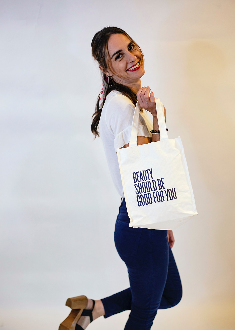 """Brittany with her Beautycounter bag that reads """"Beauty should be good for you"""""""