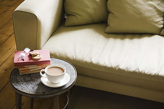 a photo of a sofa and a small table with a cup of coffee, cookies, glasses, and books