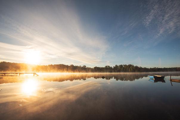 Solnedgång vid en spegelblank sjö.