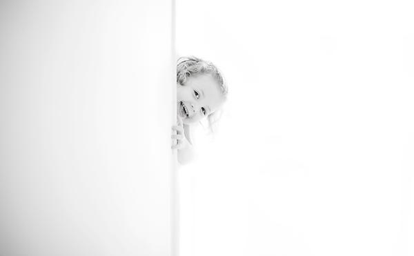 ילדה מציצה מאחורי קיר