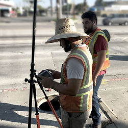 Survey crew with a GPS system near a manhole
