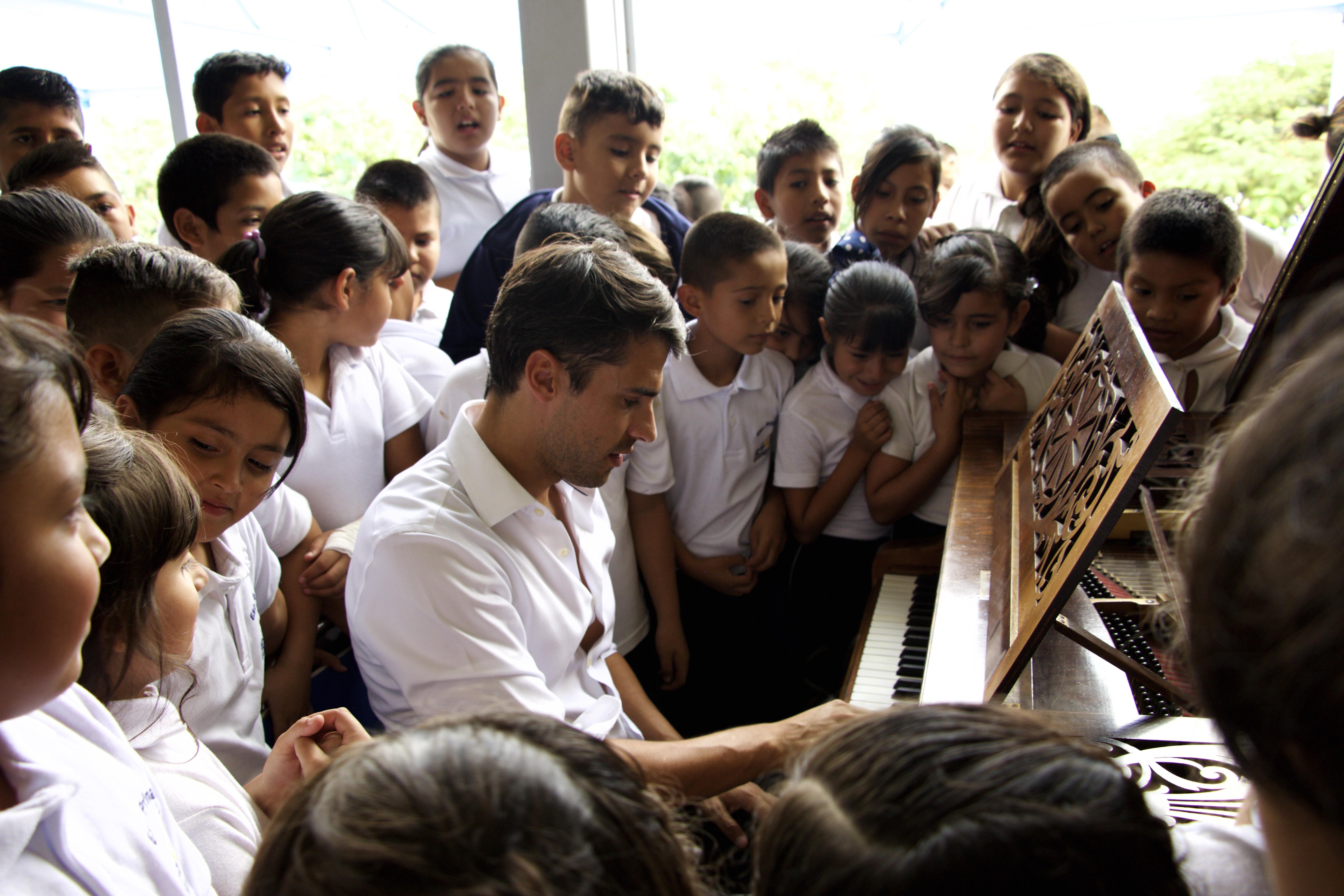 7Tocando el nuevo piano de cola de los ninos que viajo desde Suiza copie