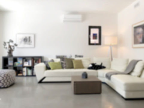 contemporary living room design with white modern couch and concrete floor