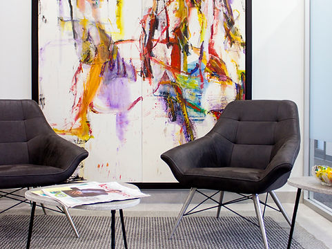 corporate office interior with stylish black leather chairs and colourful abstract painting
